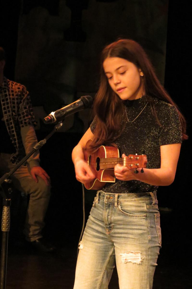 Lara zingt met haar ukulele.